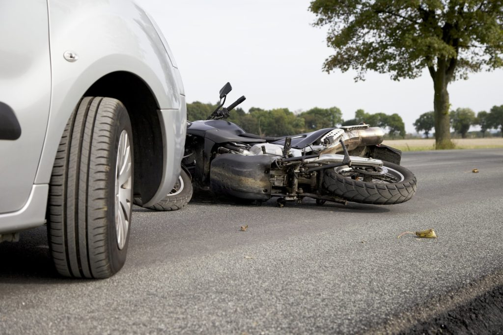 Motorcycle on the road in front of car after a collision