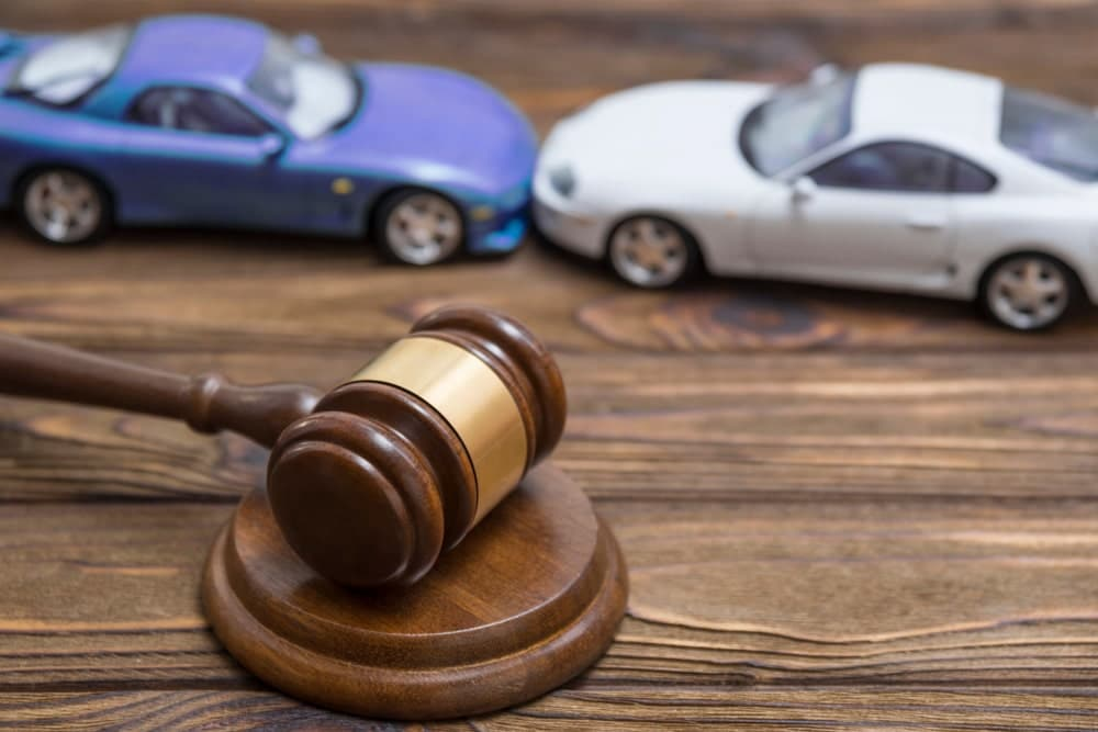 Car accident legal help concept showing a gavel with two toy cars on a desk