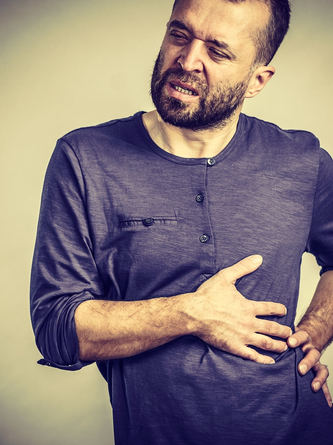 Adult guy suffering from stomach or ribs pain ache. Health problems and issues concept.